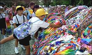 Children offer folded paper cranes at the peace memorial