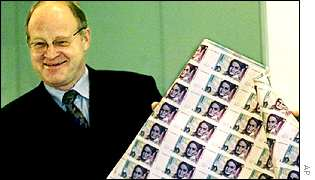 Central Bank chief Ernst Welteke displays the last print run of marks in January 2000