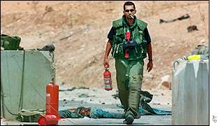 An Israeli soldiers inspect bomb site