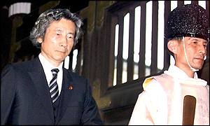Japanese Prime Minister Junichiro Koizumi led into Yasukuni Shrine by a priest