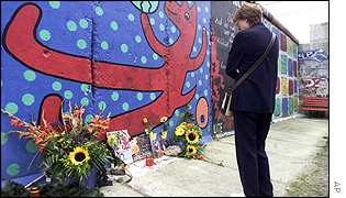 A woman lays wreaths at the Berlin Wall on Potsdamer Street