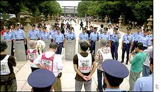 Japanese ultra leftist students group members opposed to the visit are surrounded by riot police in front of the shrine