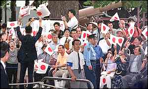 People shout banzai and wave the national flags as they welcome Prime Minister Koizumi at Yasukuni Shrine