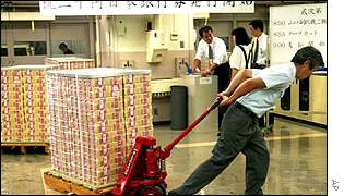 A Bank of Japan worker moves banknotes