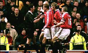 Manchester United players surround referee Andy D'Urso after he awards a penalty against them
