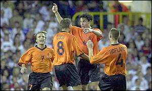 Van Bommel is mobbed after scoring against England