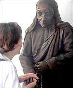 A Missionaries of Charity volunteer in front of a statue of Mother Teresa in Calcutta