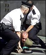 A police officer tackles a man outside the court