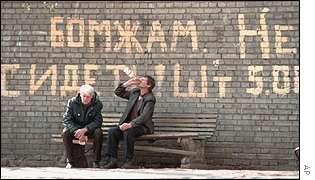 Russia homeless people sit on a bench drinking