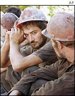 Miners sit in a line after being brought to surface