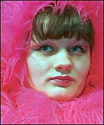 A model with pink boa feathers around her head