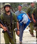 Israeli troops escort a settler to site near Hebron, West Bank