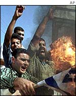 Palestinians burning an Israeli flag