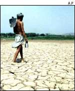 Man walks across drought-scarred lakebed AP