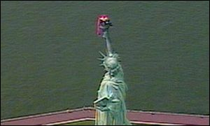 A paraglider caught on the torch of the Statue of Liberty
