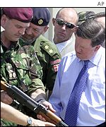 Lord Robertson (right) examines collected weapons with Nato forces