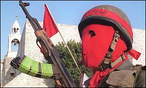 Armed PFLP supporter in a red mask at the funeral of Abu  Ali Mustafa