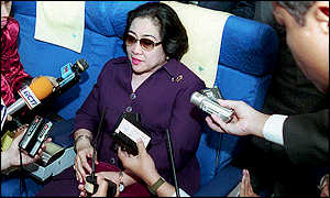 Indonesian President Megawati Sukarnoputri surrounded by journalists on the plane back to Indonesia