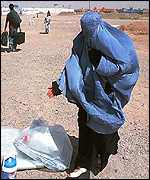 An Afghan refugee picks up her belongings
