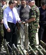 Nato Secretary General George Robertson looks at weapons handed in