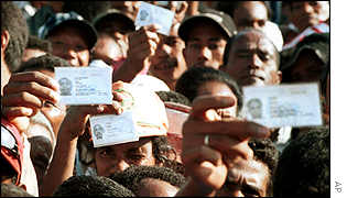Voters wave their identity cards