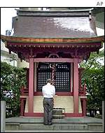 A Japanese man prays before the Tokyo's Kabuto shrine, seen as the guardian of commerce, on the day after Tokyo's Nikkei index hits a 17-year low