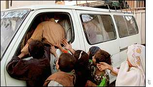 Afghan children beggars surround a vehicle of aid workers leaving their NGO office in Kabul on Saturday