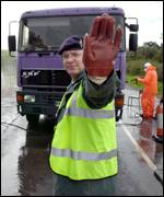 Soldier stands in front of lorry being disinfected