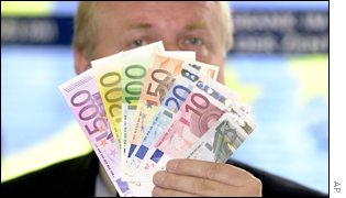 Euro banknotes being held up