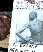 A woman holds a poster against slavery at the UN Racism Conference