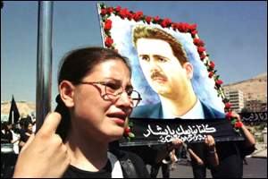 Syrian woman holding poster of President Bashar