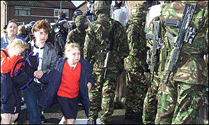 Children are shielded by the army on their way to school
