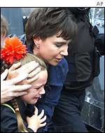 A child is swept up by her mother in Ardoyne