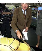 Franz Beckenbauer slices a car-shaped cake