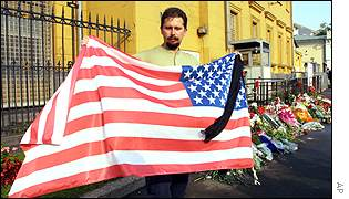 Man with US flag and black ribbon at US embassy in Moscow