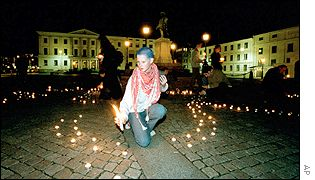 Woman lights candle in Gothenburg