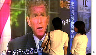 Japanese women watch coverage on giant TV screen