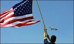 Man waving flag at US plane