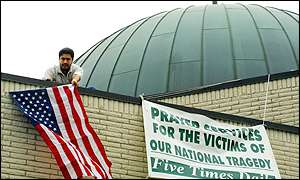 Muslim man hangs US flag from a mosque