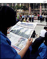 Malaysian worker reads about US attack