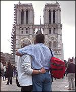 A couple observes the silence at Notre Dame cathedral