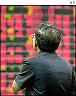 An investor watches the board at the Thai Stock Exchange in Bangkok