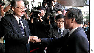 North Korea's Kim Ryong Song (r) shakes hands with South's Unification Minister Hong Soon-young