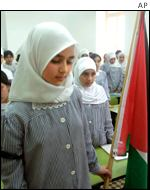 Palestinian school girls stand for a moment of silence in the West Bank