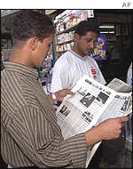 Iraqi men read reports of the attacks on the US