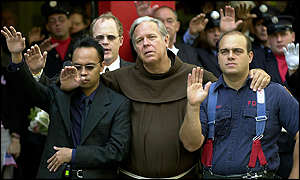 Father Christopher Keenan, centre, participates in the funeral for Mike Judge