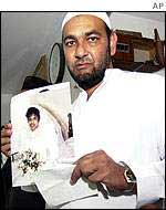 A Muslim leader holds the photo of Amena Rasul, a victim of the WTC collapse