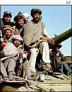 Taleban fighters sitting on a Russian-made tank