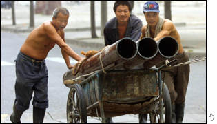 Chinese workers push a cart with pipes loaded along a street of Beijing