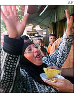 A Palestinian woman receives celebratory sweets after Tuesday's attack